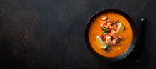 Tom Yam Kung Spicy Thai Soup With Shrimp In A Black Bowl On A Dark Stone Background, Top View, Copy Space