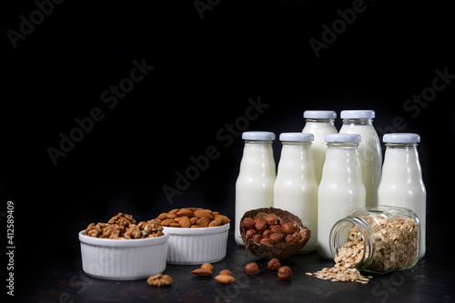 a variety of lactose-free milk from nuts and grains in glass bottles. dark vegan concept with a milk drink made from hazelnuts, oats, coconut, almonds, walnuts, rice