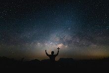 Silhouette Human Praying And Holding Christian Cross For Worshipping God At Night Landscape With Colorful Milky Way.