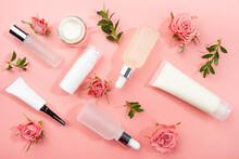 Flat Lay Cosmetic Bottles And Containers With Roses And Green Leaves On Pink Background