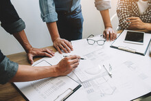 Midsection Of Architects Preparing Blueprints On Table