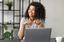 Pretty Charming Young African American Woman With Afro Hairstyle Sitting At The Desk And Looking In The Window, Taking A Break From Working On A Laptop, Dreaming About Vacation, Enjoying Her Workplace