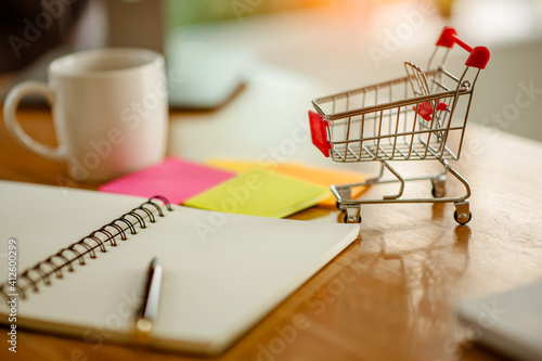 Canvas Close-up Of Open Book By Small Shopping Cart On Table