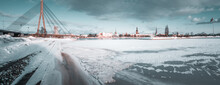 Beautiful View Of The Frozen River With Sea Gulls Sitting On The Ice By The Old Town Of Riga In Latvia.
