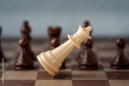 Canvas Print white chess castle falling on chess board concept of failing.