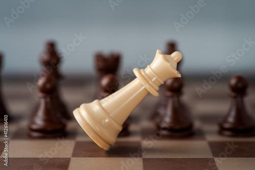Fotografija white chess castle falling on chess board concept of failing.