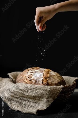 Obraz na plátně hand pouring flour over bread on black background