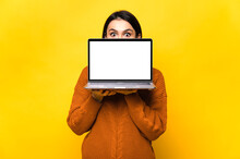 Surprised Shocked Caucasian Young Woman, Hiding Behind Blank White Screen Of Laptop, Standing On Isolated Orange Background. Copy Space.