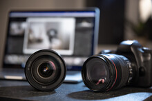 Close Up Of A Professional Digital Camera And Lens On The Desktop Of A Photographer With A Laptop.