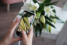 The Girl Makes A Photo On The Phone. Photographs A Bouquet Of White Lilies. Mobile Photography Training. No Visible Logos.
