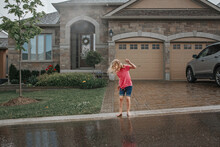 Cute Adorable Girl Splashing Under Rain In Front Of House. Child Having Fun During Rain Shower Storm. Seasonal Summer Outdoors Activity For Kids. Freedom And Happy Childhood Lifestyle.
