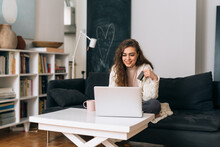 Woman Shopping Online On Laptop Computer While Sitting On Sofa In Her Home
