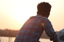 Man Looking Away While Sitting Against Sky During Sunset