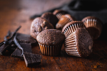 Chocolate muffins. Sweet dark cupcakes with chocolate and vanilla pods.
