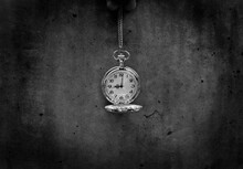 Close-up Of Pocket Watch Hanging Against Wall