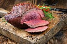 Traditional Barbecue Haunch Of Venison Sliced And As Piece Served With Tomatoes And Herbs As Close-up On A Rustic Wooden Board