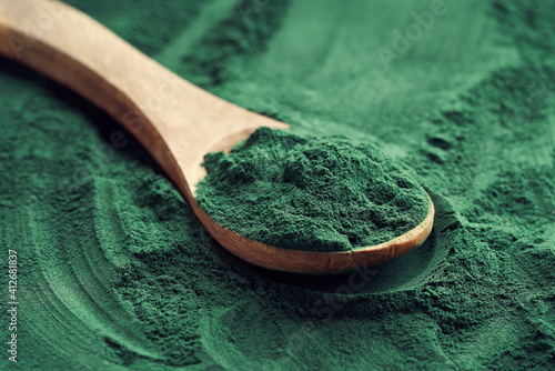 Fototapeta Fresh spirulina algae powder on a spoon on a spirulina background obraz
