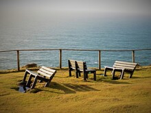 Empty Benches On Shore By Ocean Against Sky