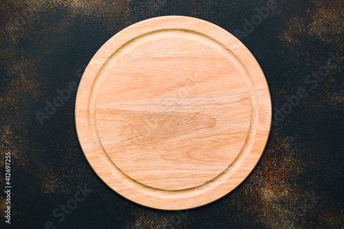 New round wooden cutting board for pizza on stone background Fototapet
