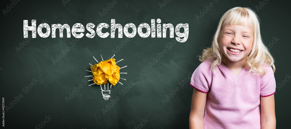 Fototapeta young smiling girl in front of blackboard with message HOMESCHOOLING