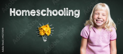 Fototapeta young smiling girl in front of blackboard with message HOMESCHOOLING obraz