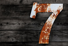 High Angle View Of Rusty Metallic Number 7 On Table