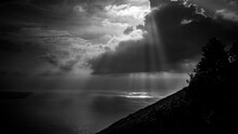 Grayscale Shot Of Sun Rays Through The Clouds