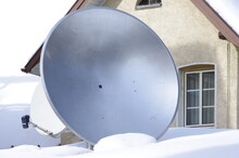 Low Angle View Of Satellite Dish On Snowy Roof