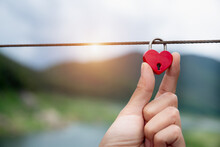 Red Heart Keys On Steel Rope, Natural Background, Love Concept, Symbolism For Valentine's Day Feeling.