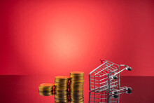 Close-up Of Coins Stack By Shopping Cart On Table Against Red Background