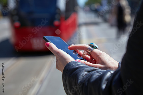 Tela Woman using cellphone on a tram station in Europe.