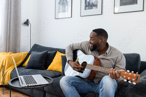 Young African American male musician or teacher playing guitar during an online Fototapeta