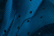 Black Mesh Fabric In Small Peas On A Blue Background Wrinkled As A Background Macro