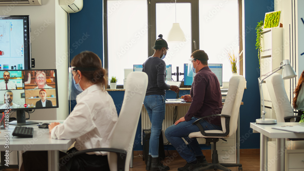 Fototapeta Business woman discussing on webcam using wireless headphone with remotely partners wearing protective mask sitting in modern office. Having videocall, colleagues working respecting social distance