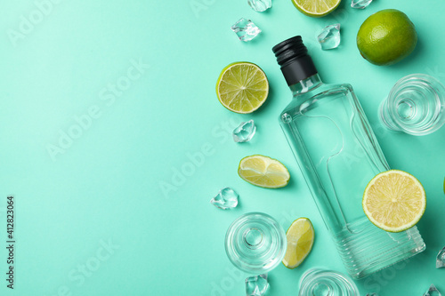 Bottle and shots of vodka, limes and ice on mint background, top view © Atlas