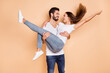 Photo of pretty married couple dressed white t-shirts dancing he holding arms her looking each other isolated beige color background