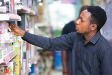 Young Black Man Picking Up An Item Form A Shelf In A Supermarket