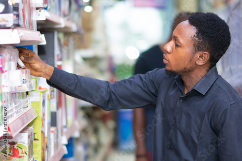 Fototapeta young black man picking up an item form a shelf in a supermarket