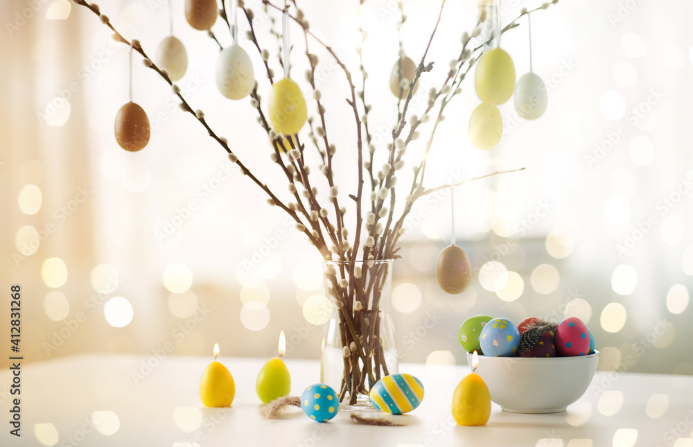 Fototapeta holidays and object concept - pussy willow branches decorated by easter eggs in vase and candles on table over bokeh lighs