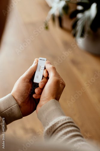 Fototapeta man at home checks a covid-19 rapid antigen device obraz