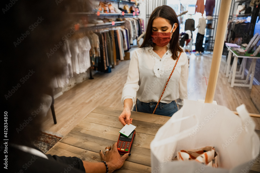 Fototapeta Customer in clothes shop pays to saleswoman at cashier with credit card with contactless payment wearing protective face masks during global Coronavirus Covid-19 pandemic
