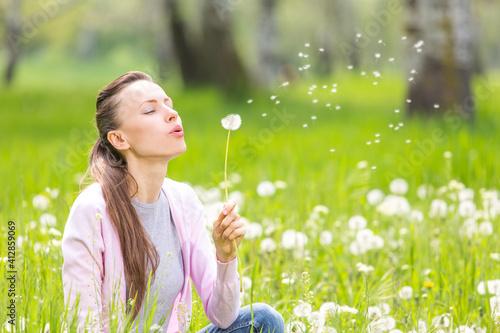 Canvas-taulu Beautiful woman in the dandelion field, woman blow a dandelion