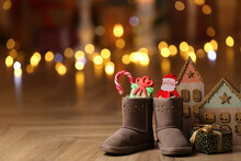 Boots Filled With Sweets And Gift On Floor In Room, Space For Text. Saint Nicholas Day
