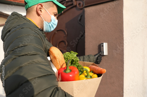 Courier in medical mask holding paper bag with groceries and ringing doorbell outdoors. Delivery service during quarantine due to Covid-19 outbreak © New Africa