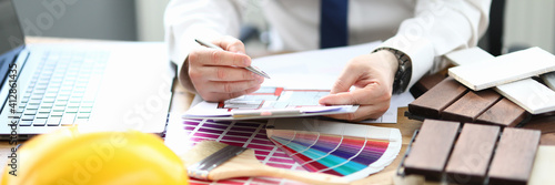 Obraz Designer in office sits at table with project and a color palette for the interior. Planner apartment houses offices concept - fototapety do salonu