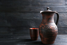 Brown Clay Jug And Cup On Black Wooden Table. Space For Text