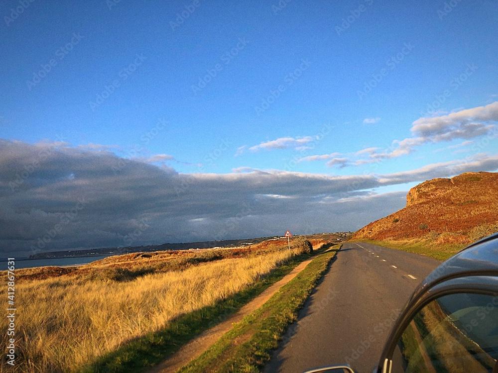 Fototapeta Road Amidst Field Against Blue Sky