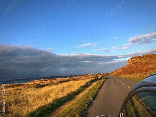 Fototapeta Road Amidst Field Against Blue Sky obraz
