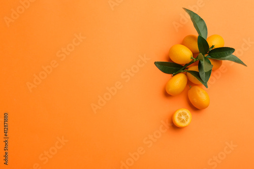 Fototapeta Fresh ripe kumquats with green leaves on orange background, flat lay. Space for text obraz