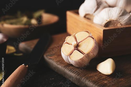 Fototapeta Wooden board with garlic on table obraz
